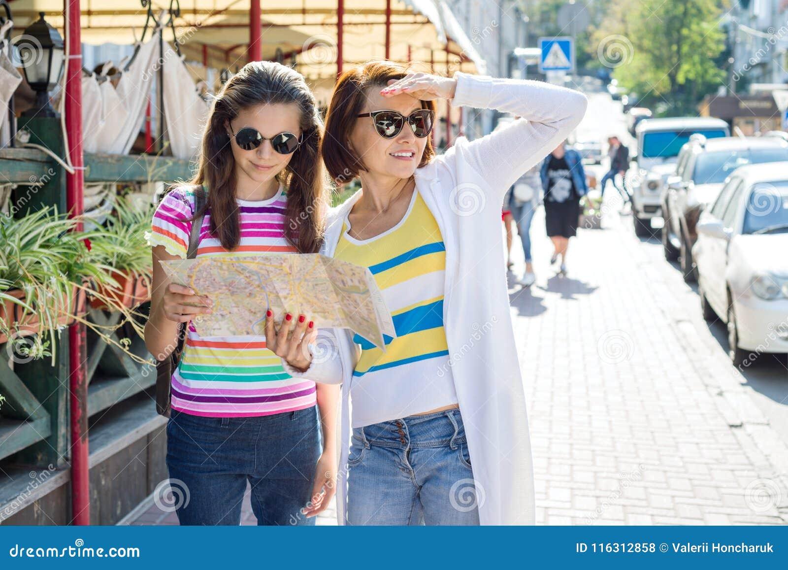 A mãe e a filha adolescente na rua da cidade olham o mapa Família de viagem