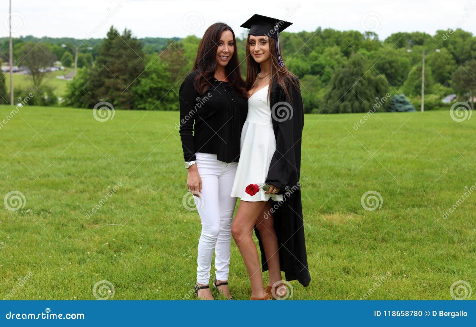 Mãe e filha bonitas no tampão, no vestido e em Tass pretos, adolescente  sexy  Cara lindo original, sorriso agradável, menina mar