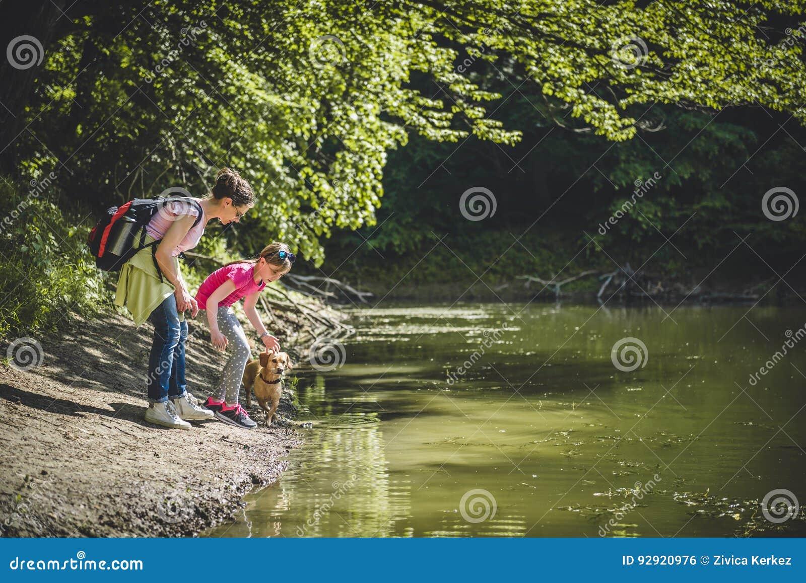 Mãe e filha com o cão pelo lago