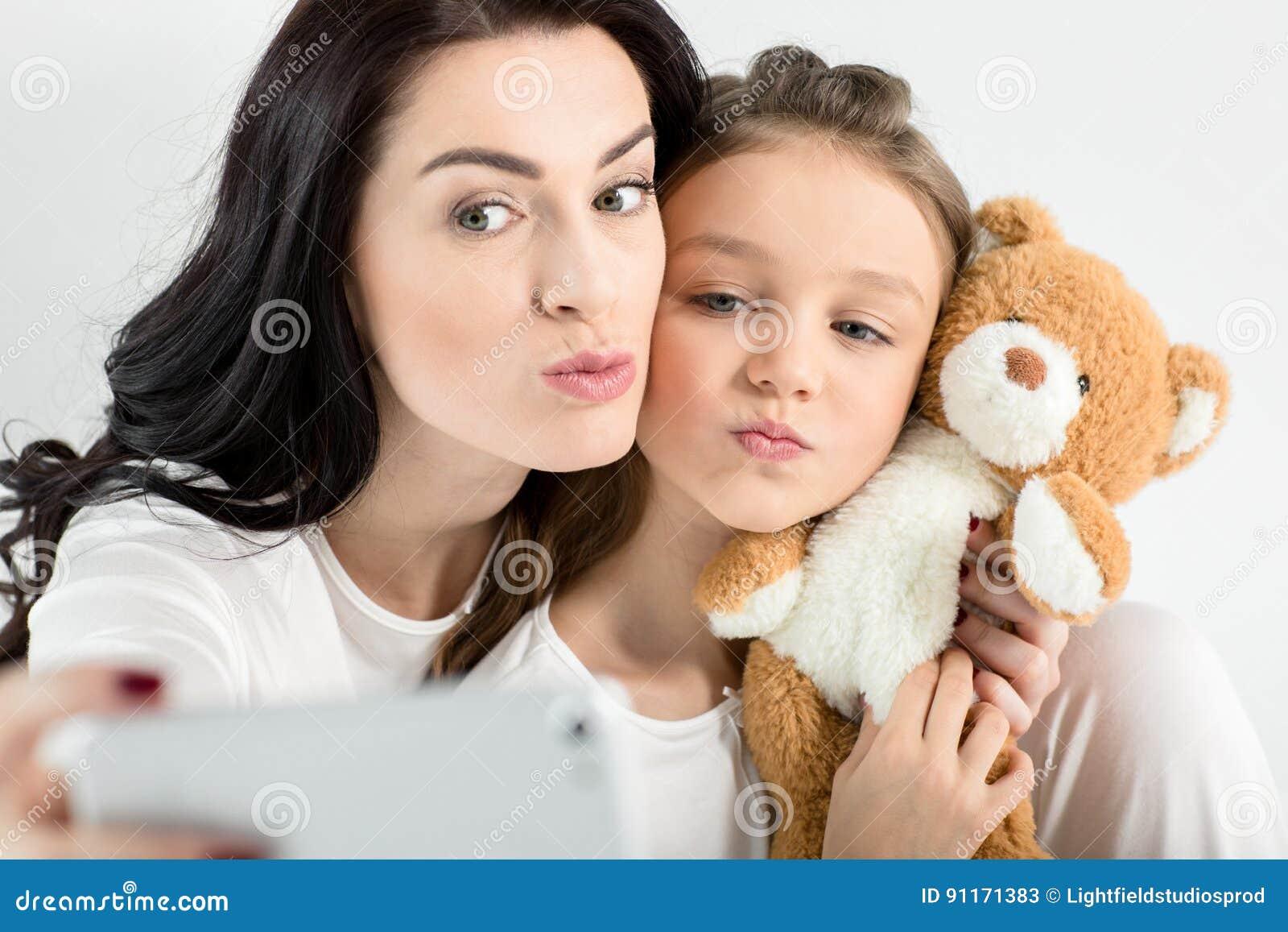 Mãe e filha com o urso de peluche que toma o selfie com smartphone