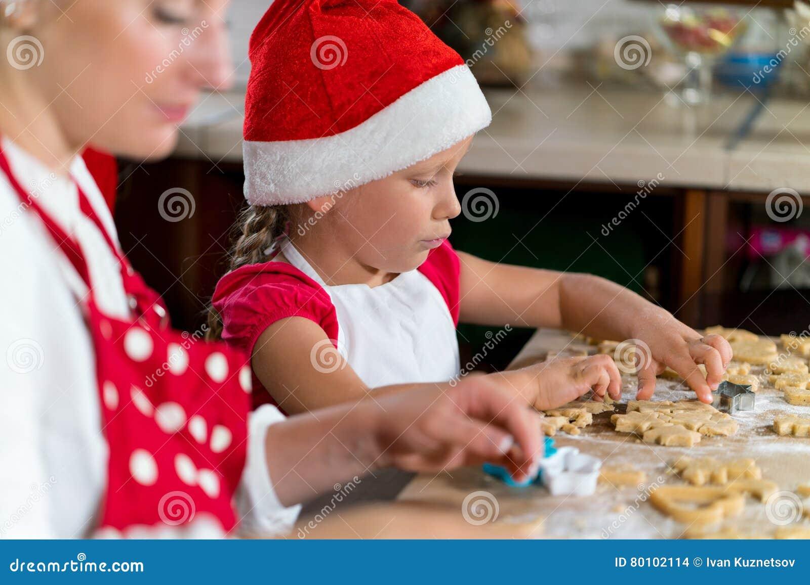 A mãe e a filha estão preparando o pão-de-espécie para o Natal