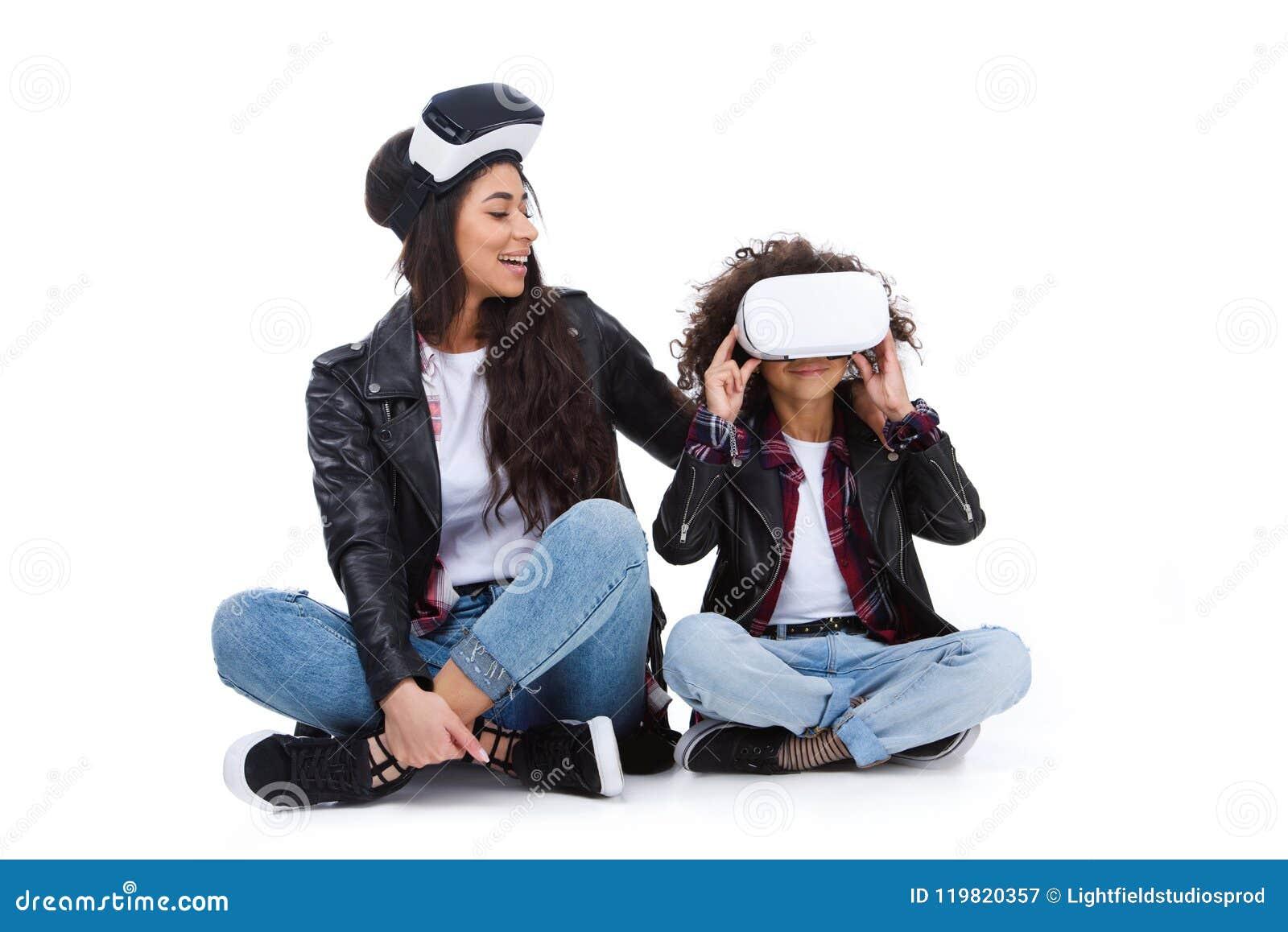 Mãe e filha felizes nos auriculares da realidade virtual que sentam-se no assoalho