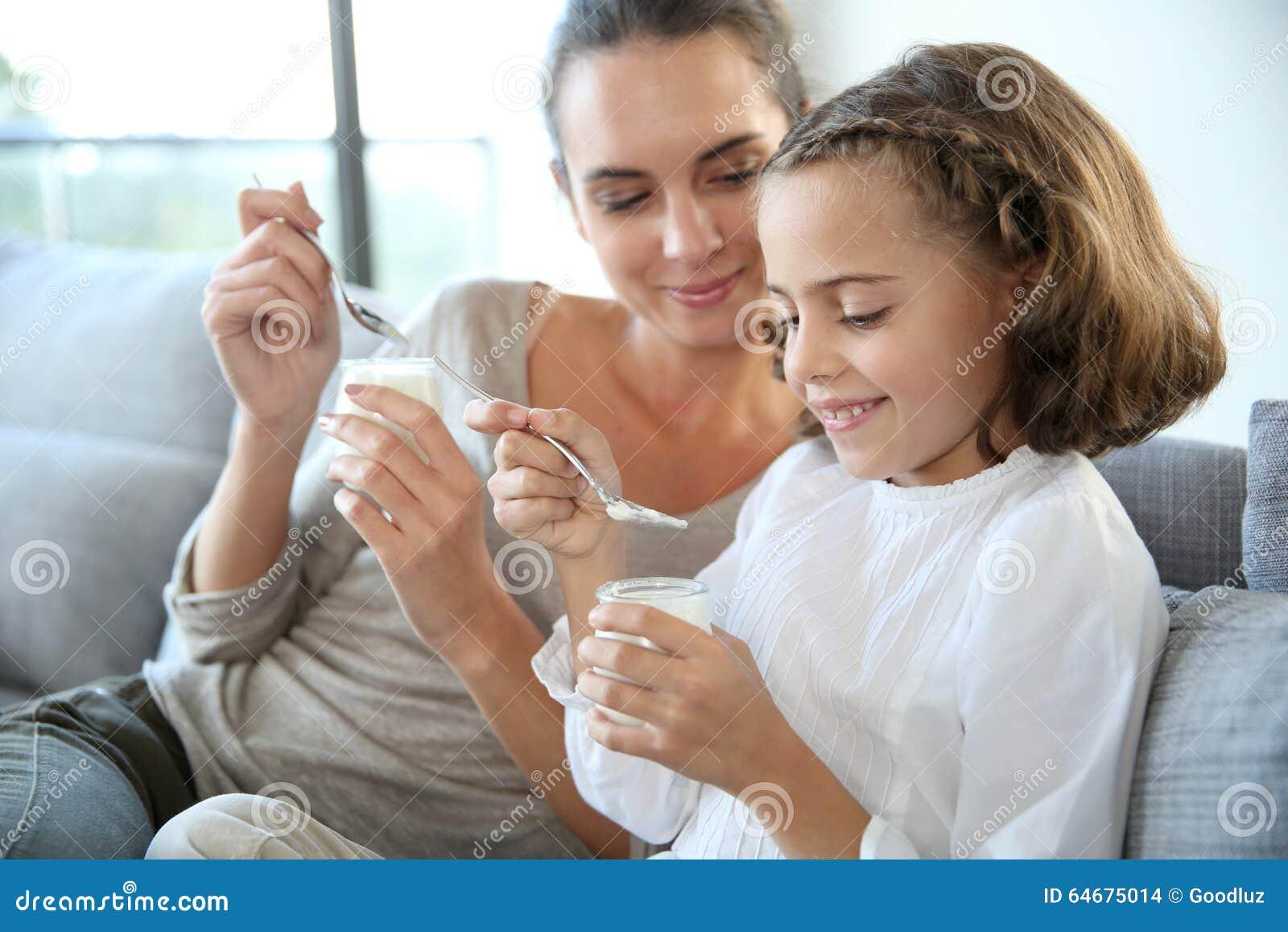 Mãe e filha que apreciam comendo o iogurte