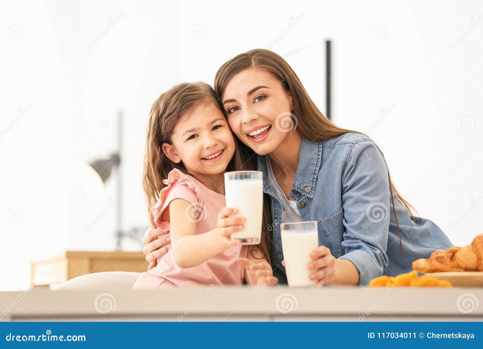 Mãe e filha que comem o café da manhã com leite