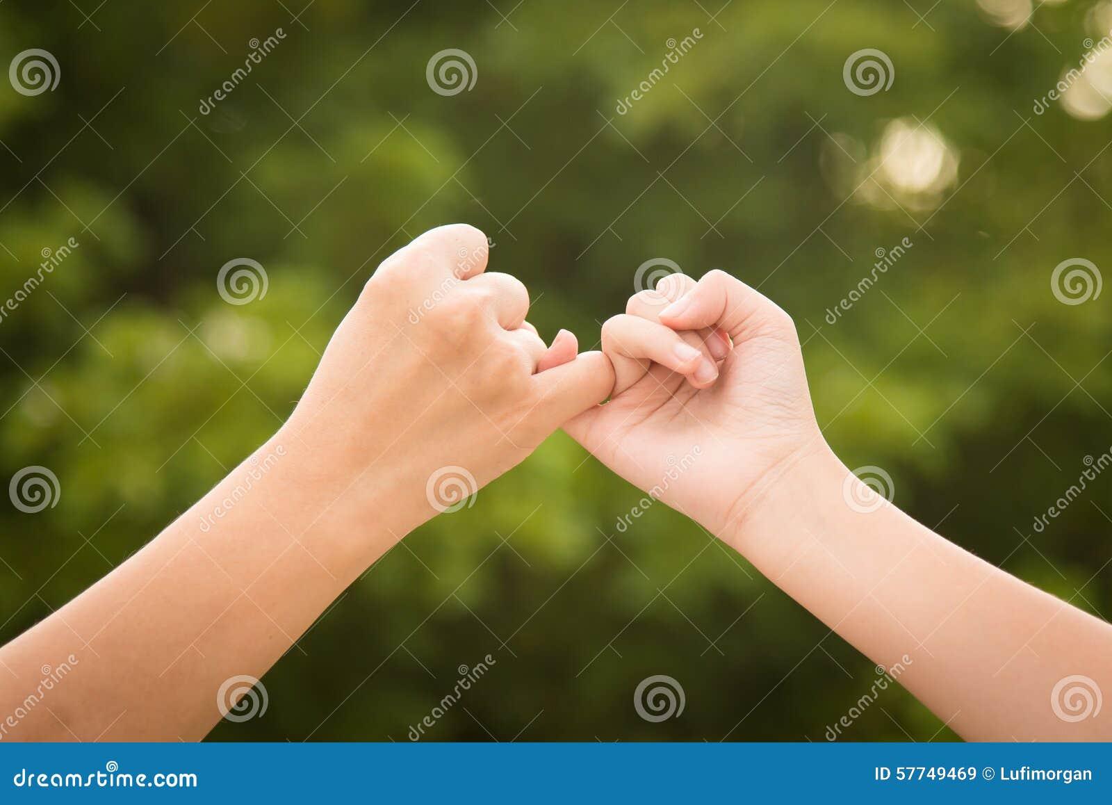 Mãe e filha que fazem uma promessa do dedo mínimo