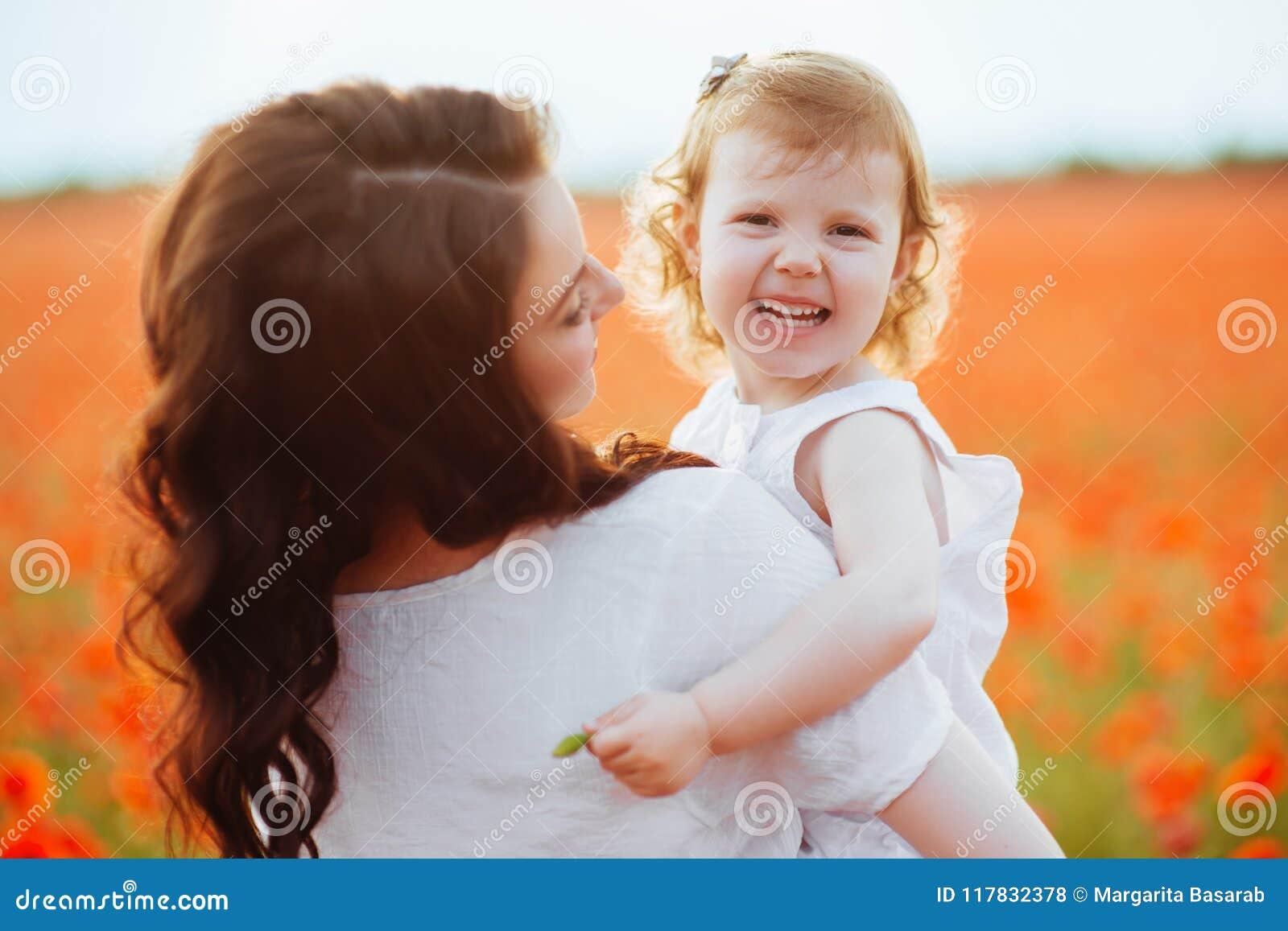Mãe e filha que jogam no campo de flor