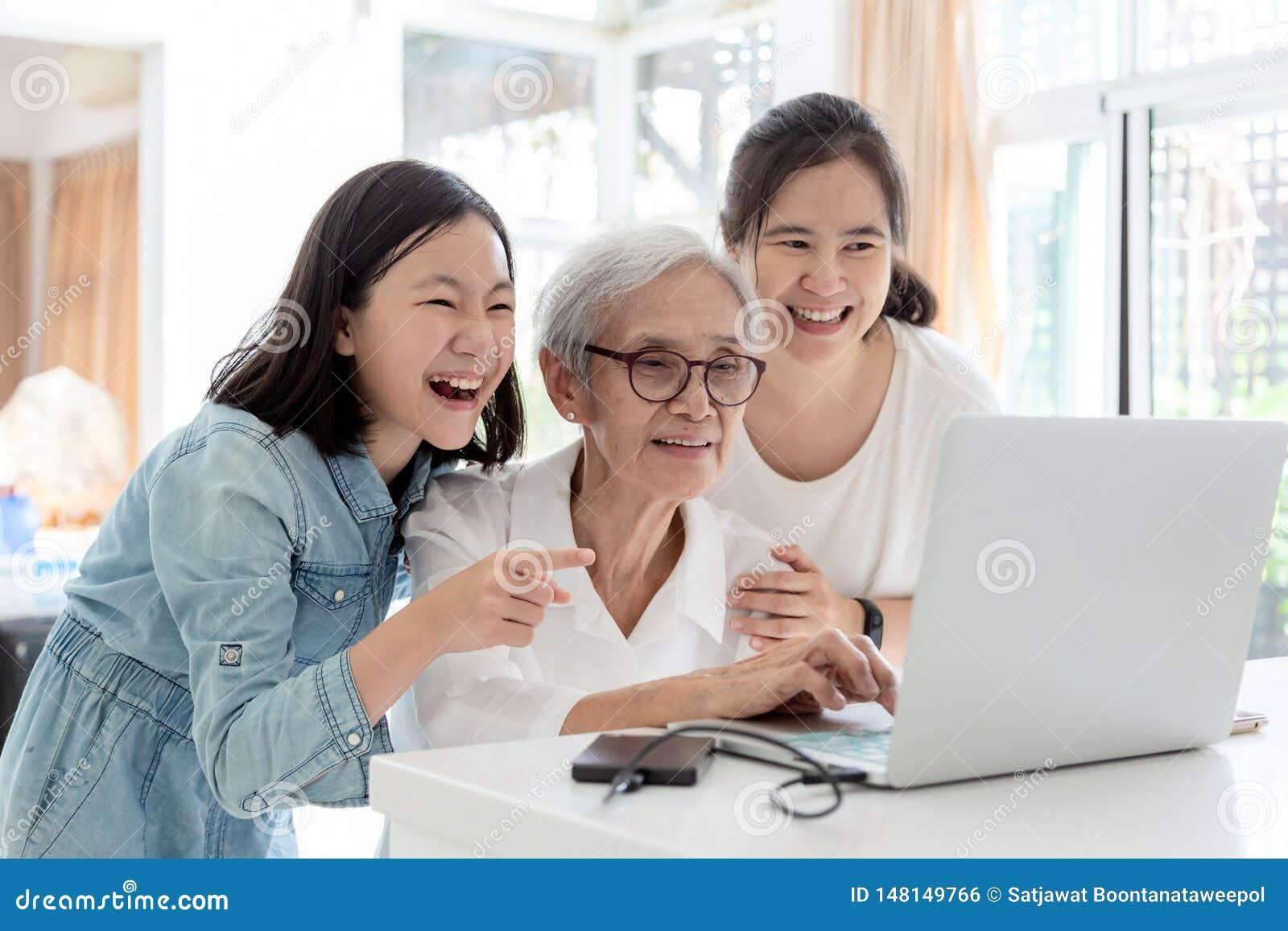 Mãe e filha que surfam o Internet; olhando algo interessante com avó, quando superior asiático de sorriso feliz da mulher