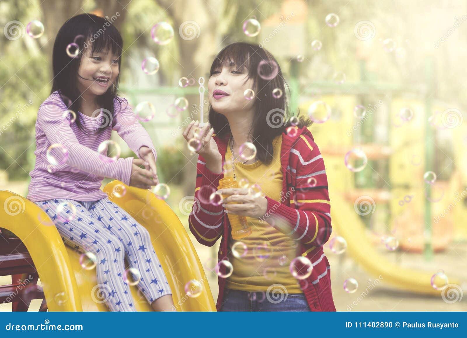 Mãe e filha que têm o divertimento com bolhas de sabão no campo de jogos