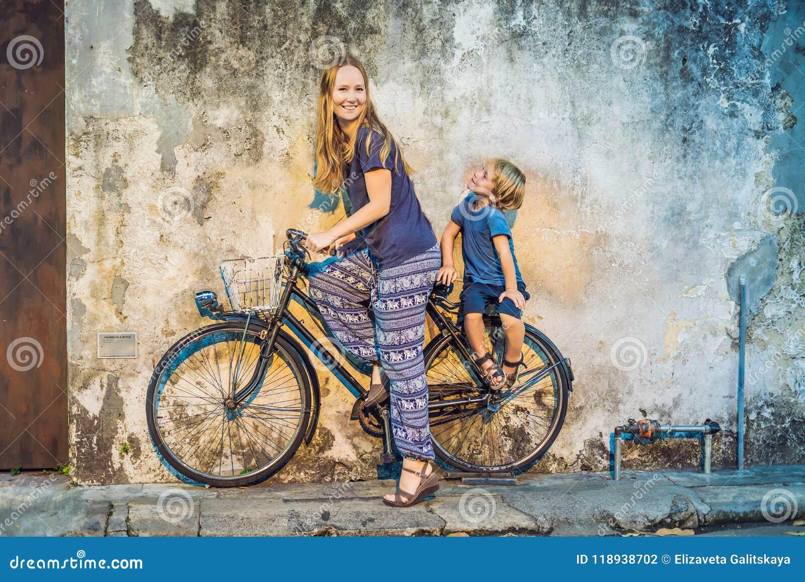 Mãe e filho em uma bicicleta Bicicleta pública da rua em Georgetown, Penang, Malásia
