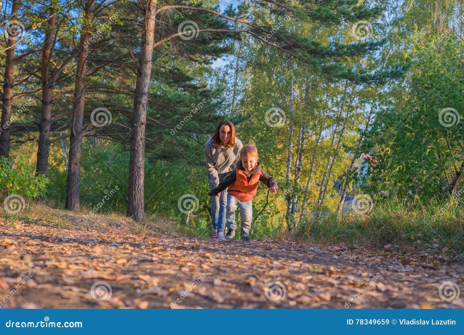 Mãe e filho que correm no trajeto na floresta do outono
