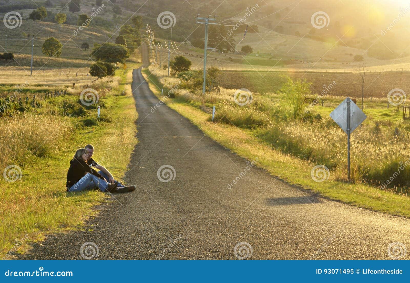 Mãe e filho que sentam-se pelo campo de observação do por do sol da estrada secundária vazia longa