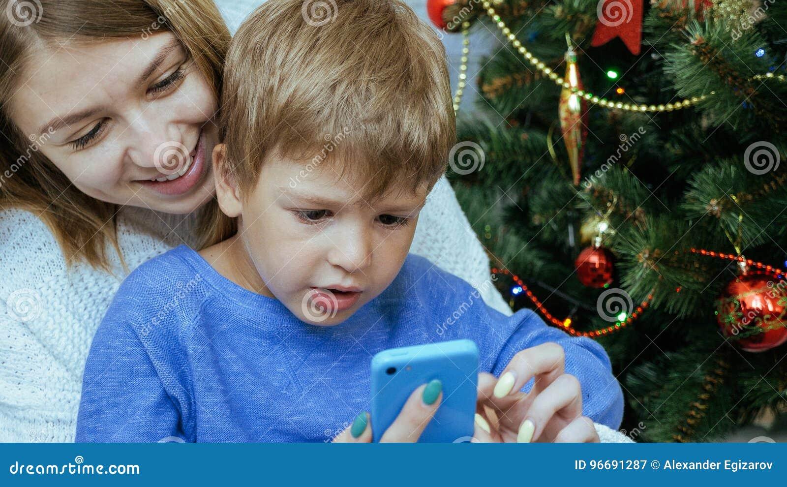 A mãe e o filho com telefone celular estão sentando-se junto perto da árvore de Natal