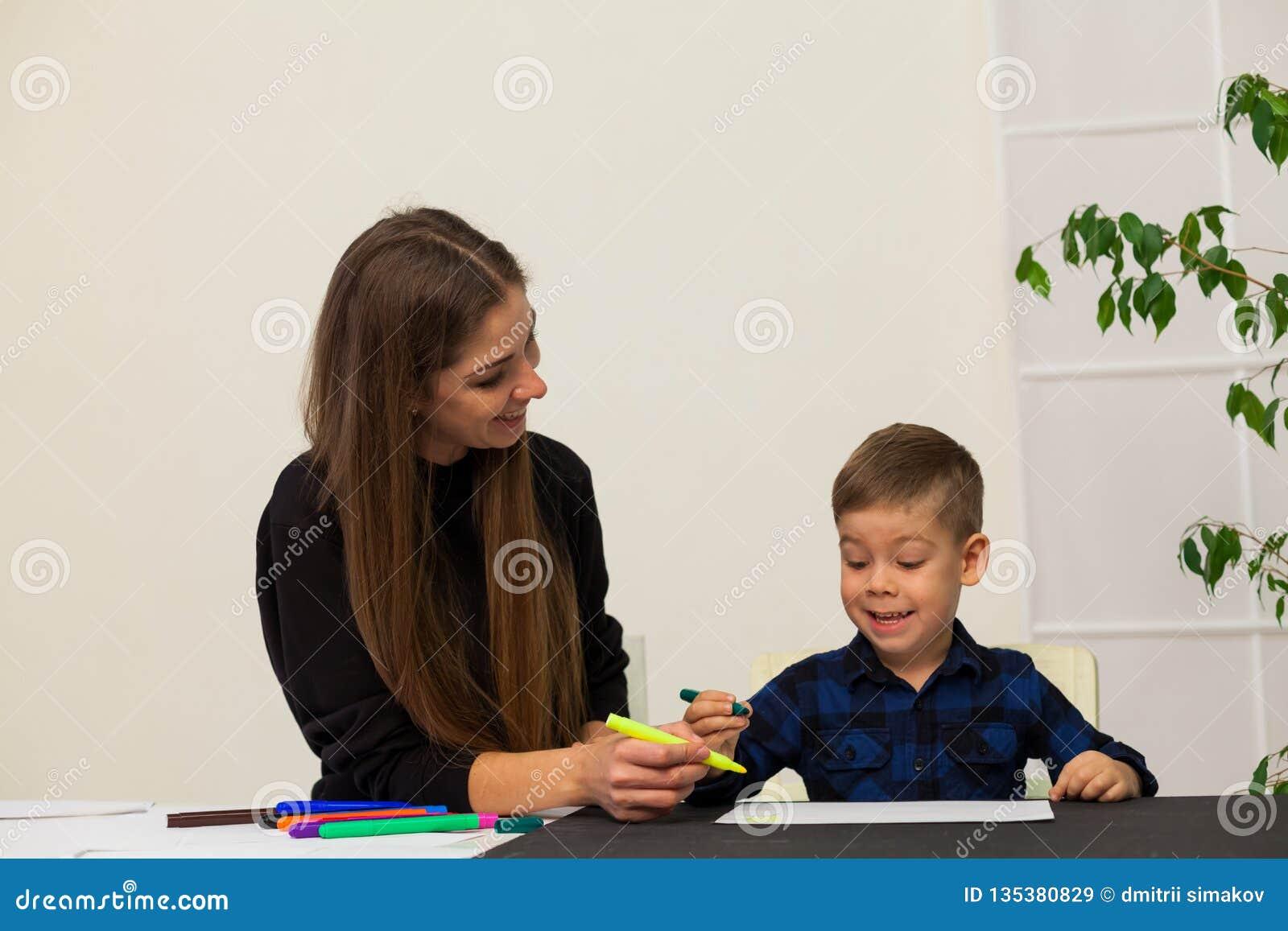 A mãe e o filho novo tiram uma imagem na tabela