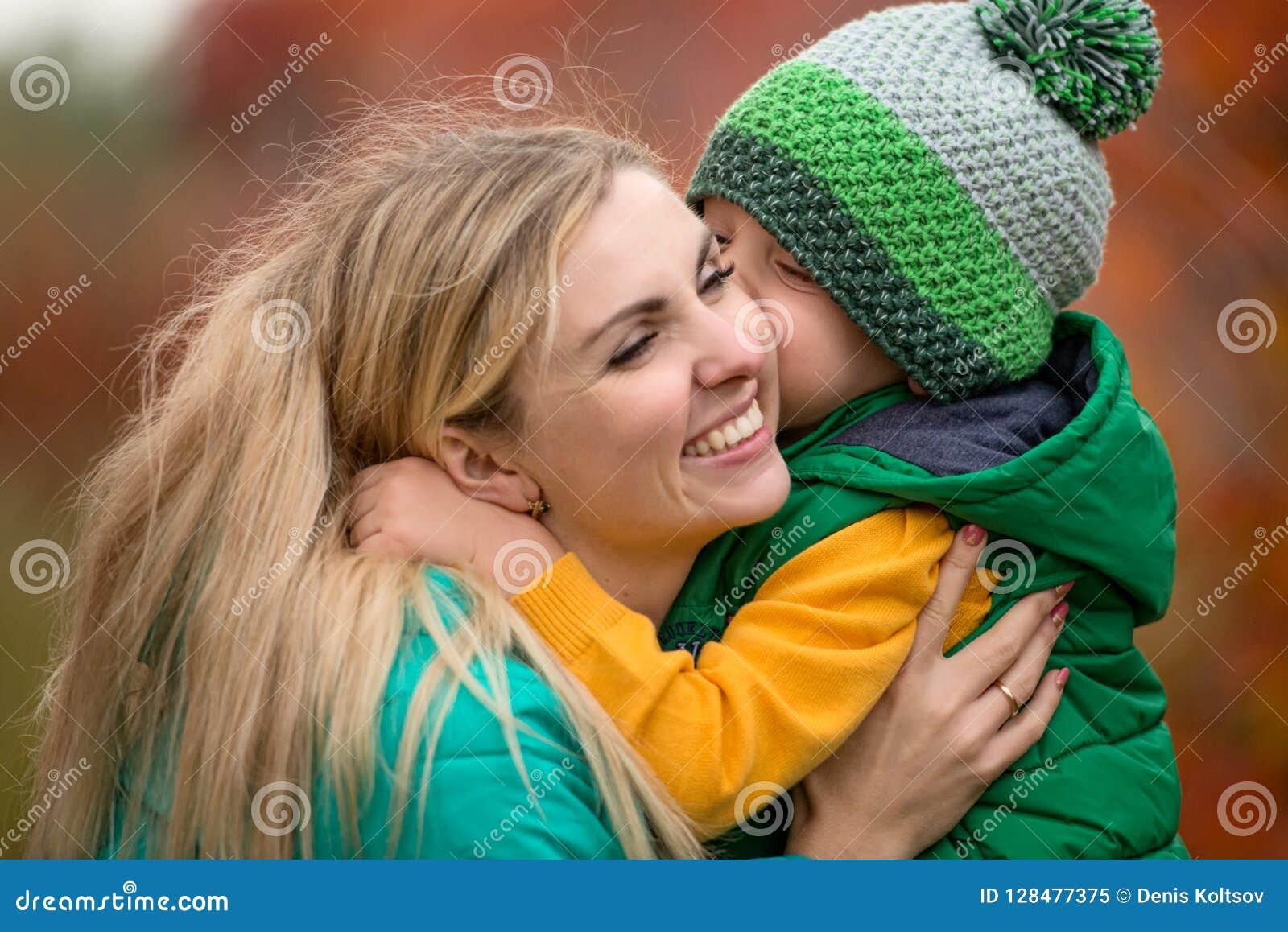 A mãe e o filho pequeno que andam no outono estacionam A criança delicadamente abraça e beija a mamã no mordente