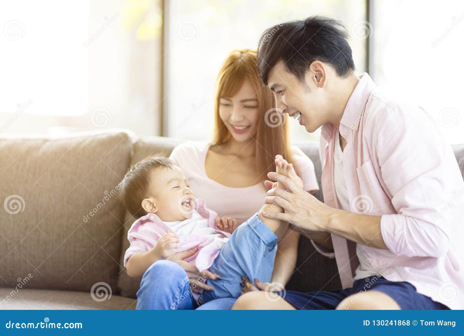 Mãe e pai da família que jogam com bebê em casa