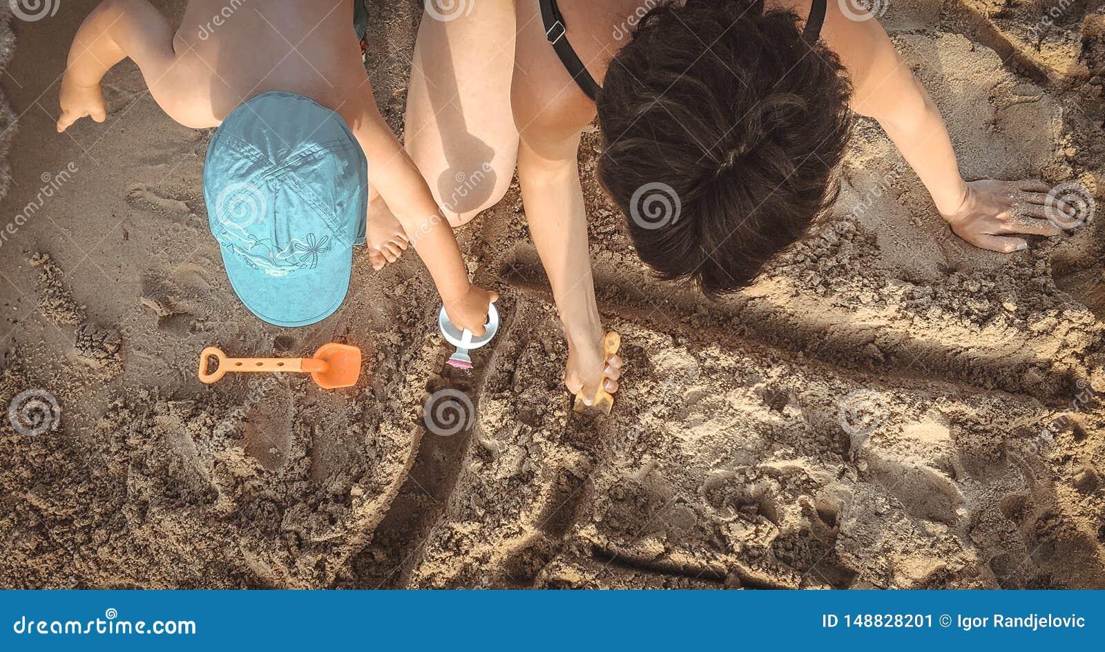 Mãe e uma criança que tem o divertimento na praia Olhe de acima