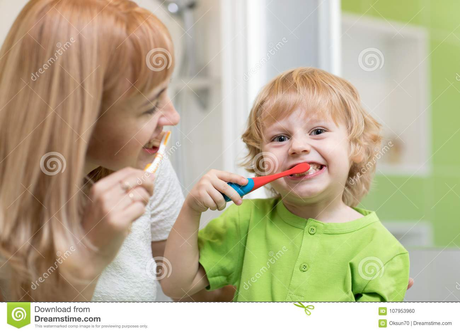 A mãe ensina a seu filho pequeno como escovar os dentes
