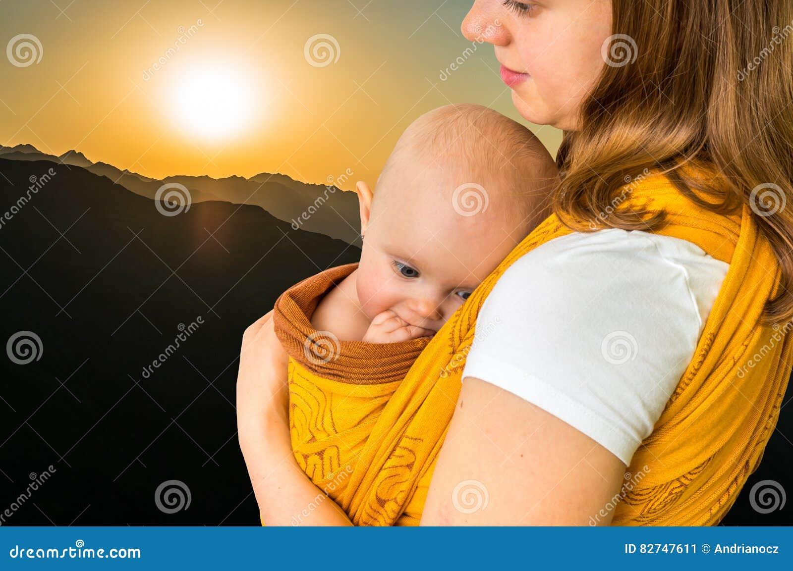 Mãe feliz com seu bebê em um estilingue