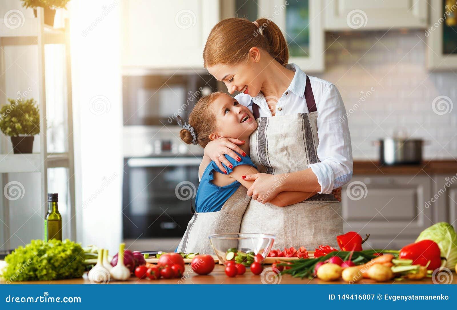 M?e feliz da fam?lia com a menina da crian?a que prepara a salada vegetal