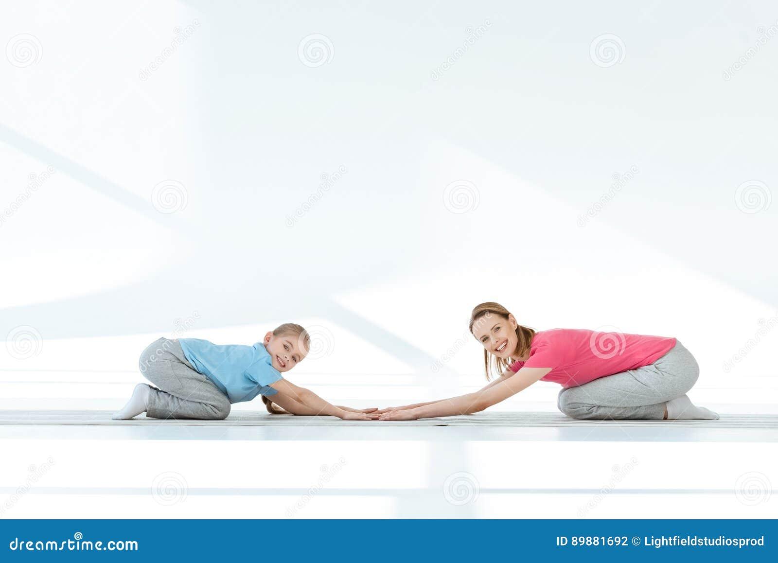 Mãe feliz e filha no sportswear que exercitam em esteiras da ioga