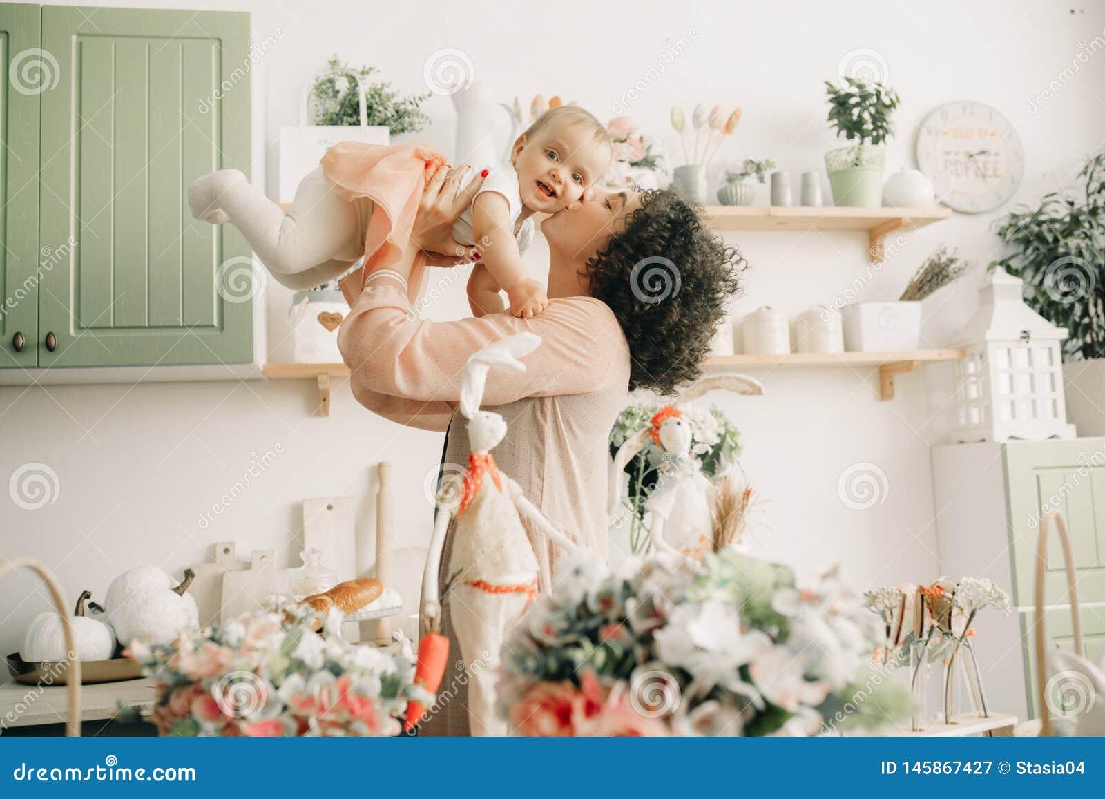 A mãe feliz joga e beija seu bebê na cozinha