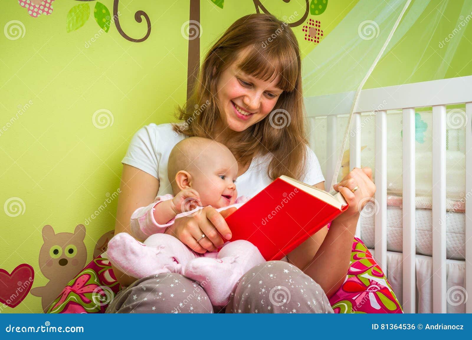 Mãe feliz que lê um livro a seu bebê
