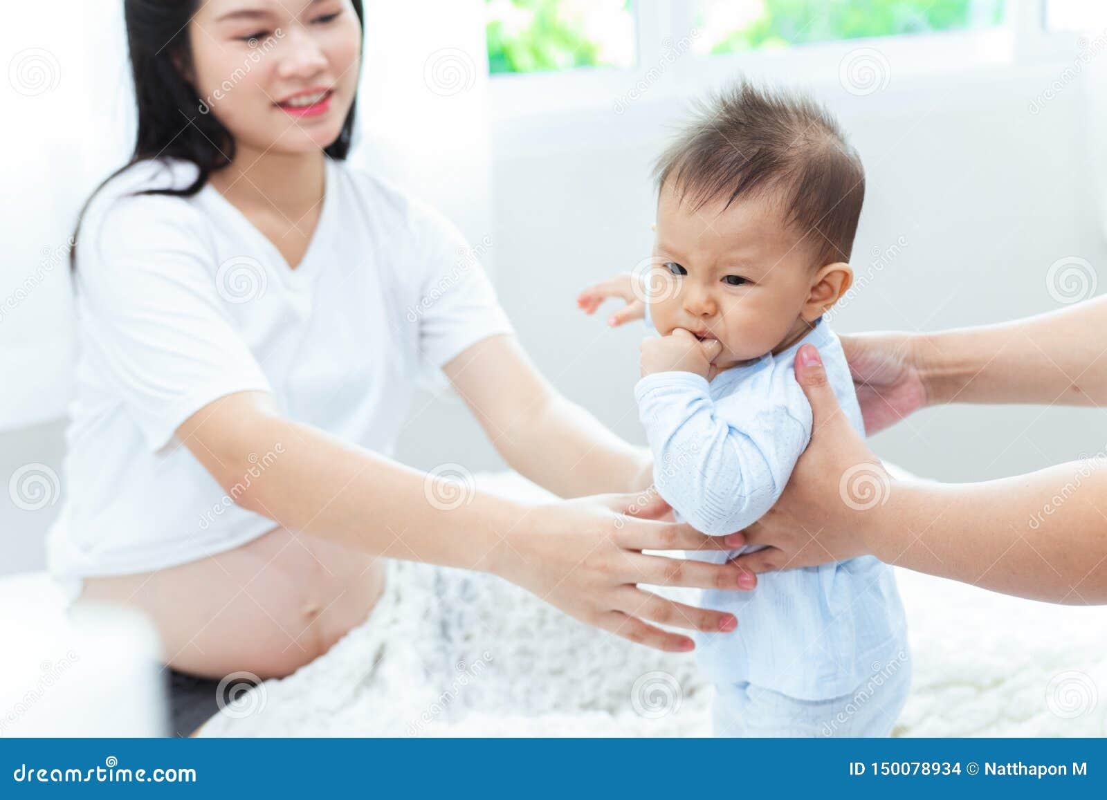 A mãe grávida está tomando seu filho levanta acima mas o menino expressou-o não foi satisfeito