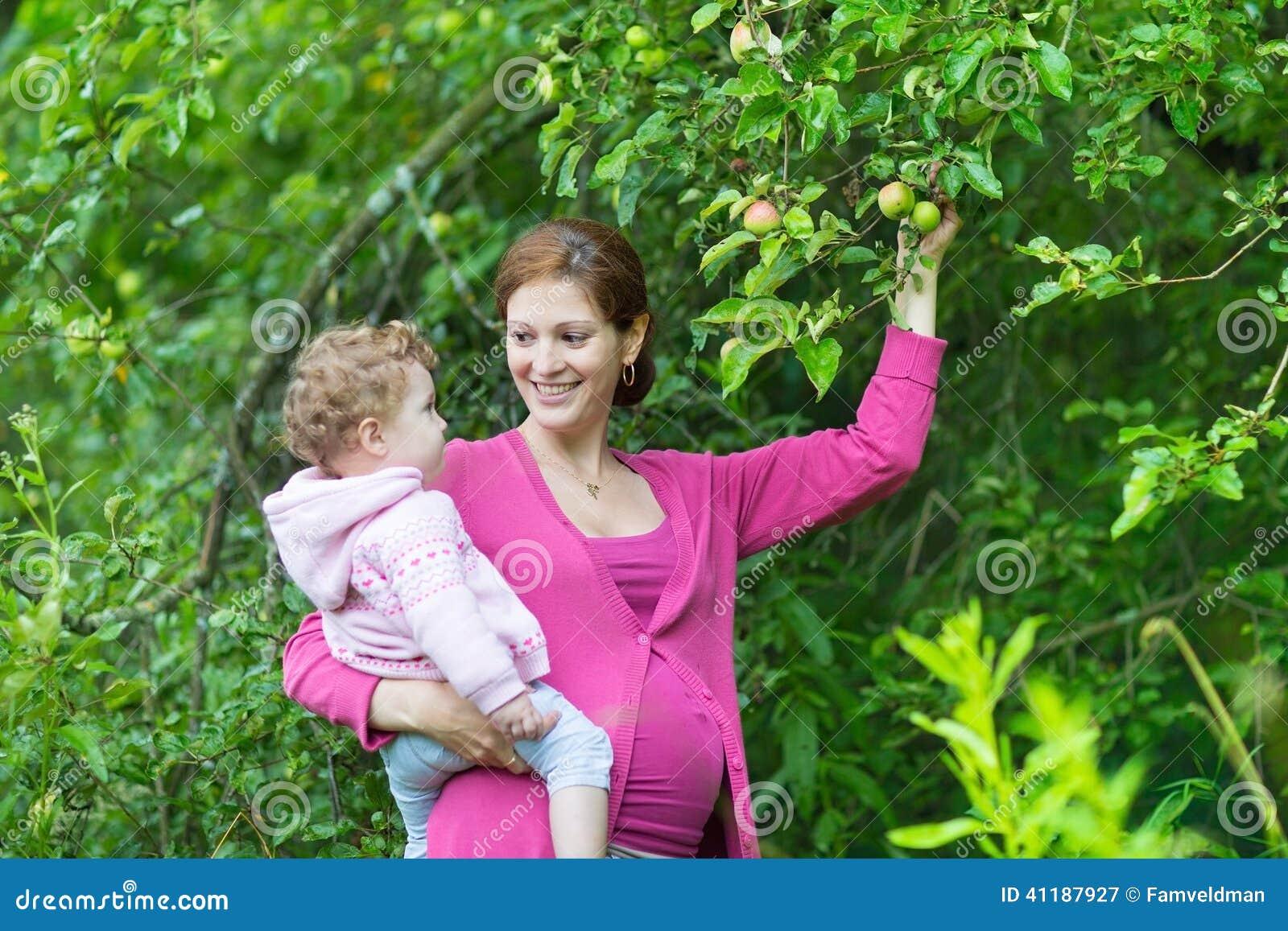 Mãe grávida feliz e sua filha do bebê do bebê de um ano