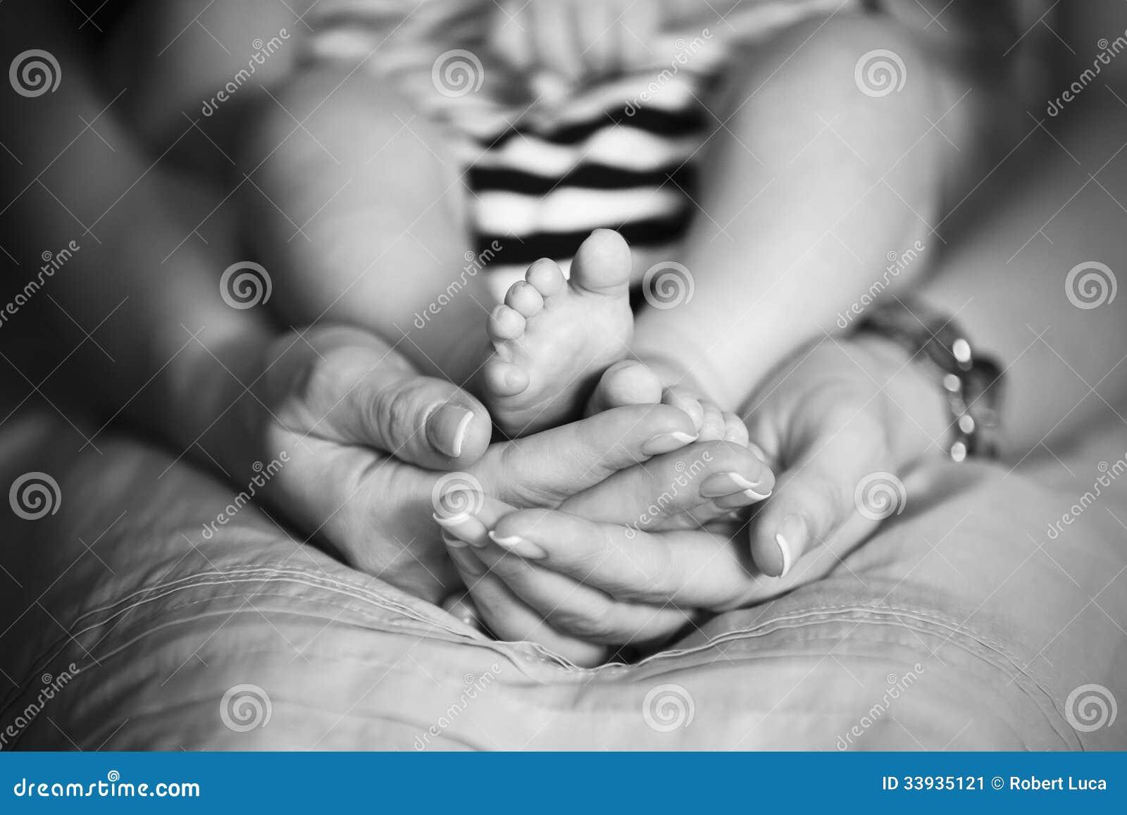 A mãe guarda os pés do bebê nas mãos