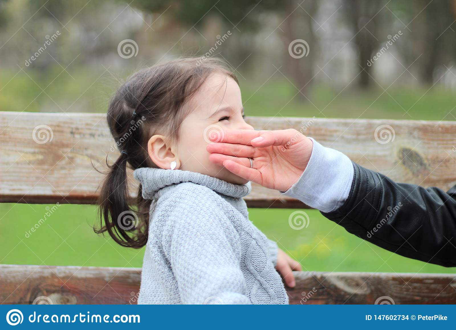 A mãe guarda sua mão no mordente de sua filha ao sentar-se em um banco no parque