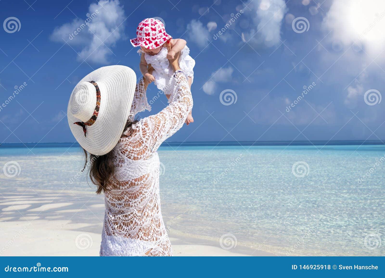 A mãe joga com sua filha do bebê na praia tropical