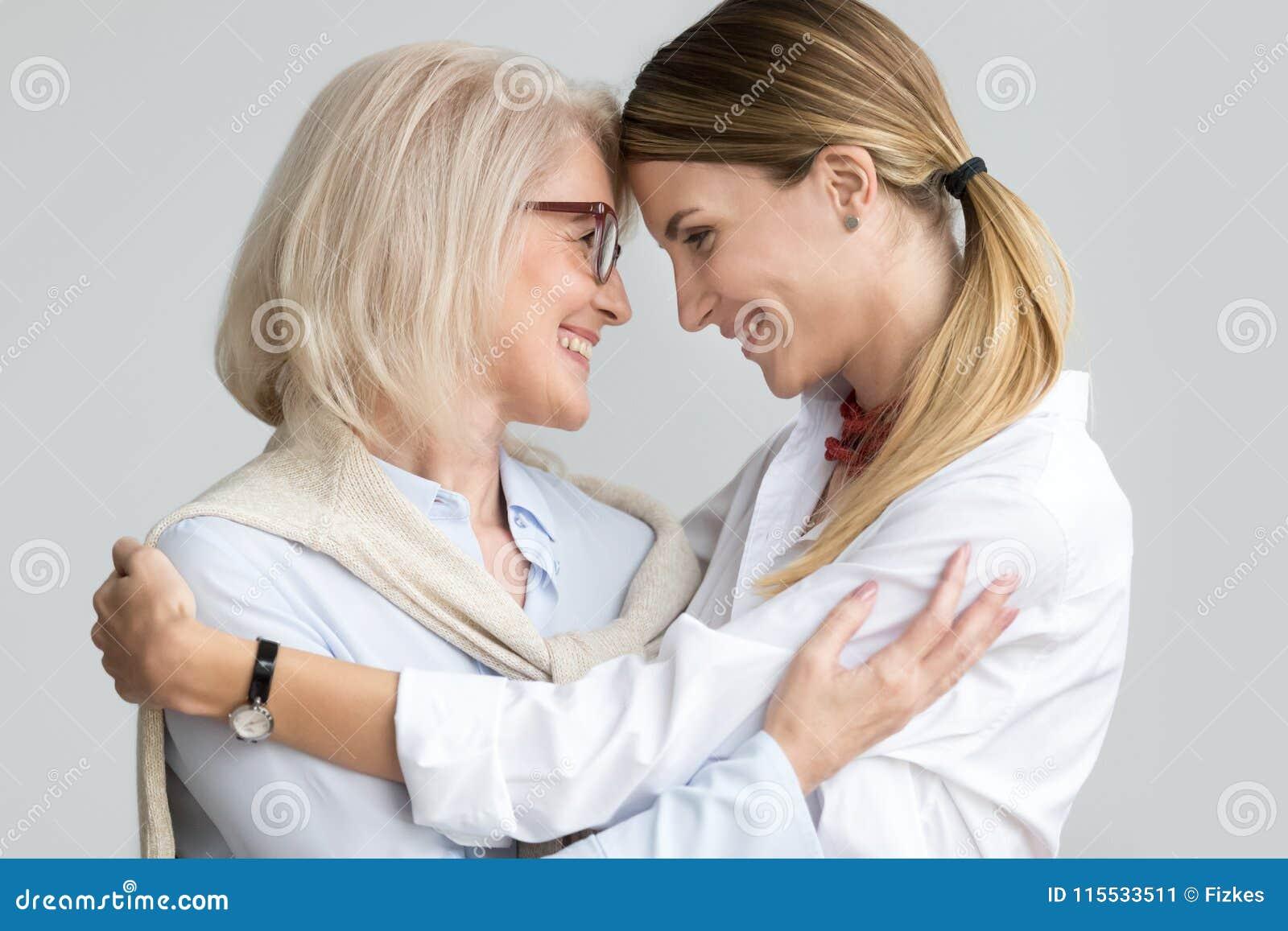 Mãe mais idosa envelhecida atrativa que abraça o touchi novo adulto da filha