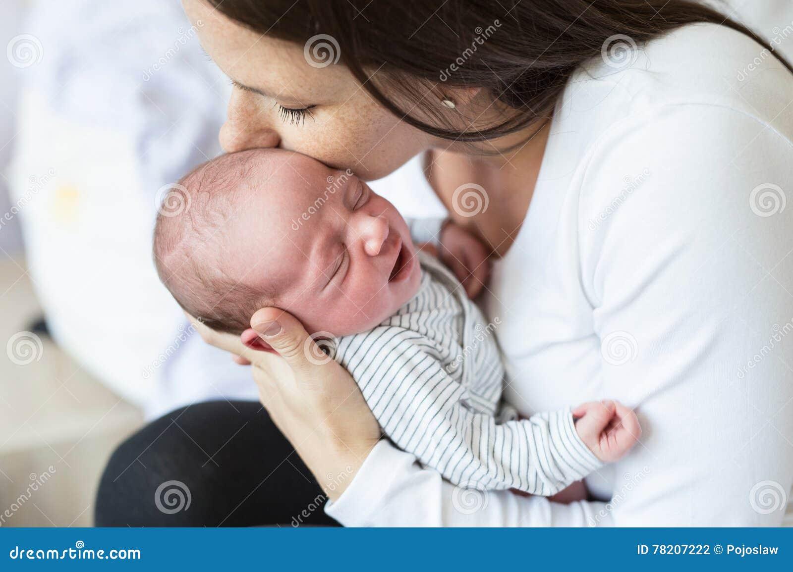 Mãe nova bonita com seu filho recém-nascido do bebê, quarto