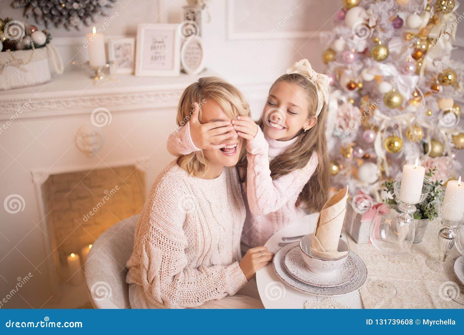 Mãe nova bonita com sua filha no interior de ano novo na tabela perto da árvore de Natal