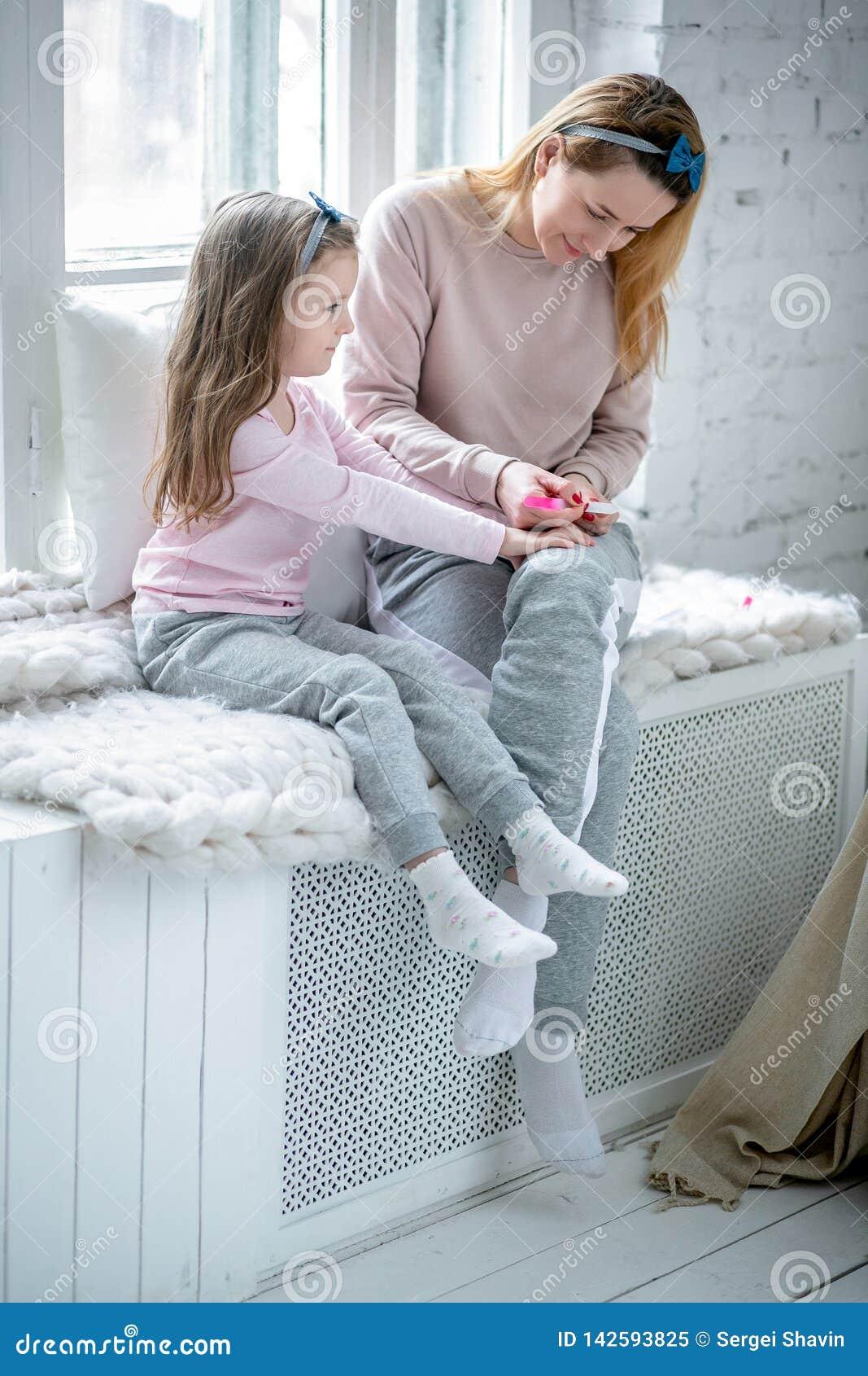 A mãe nova bonita e sua filha pequena estão sentando-se pela janela junto e estão pintando-se seus pregos Cuidado materno e amor