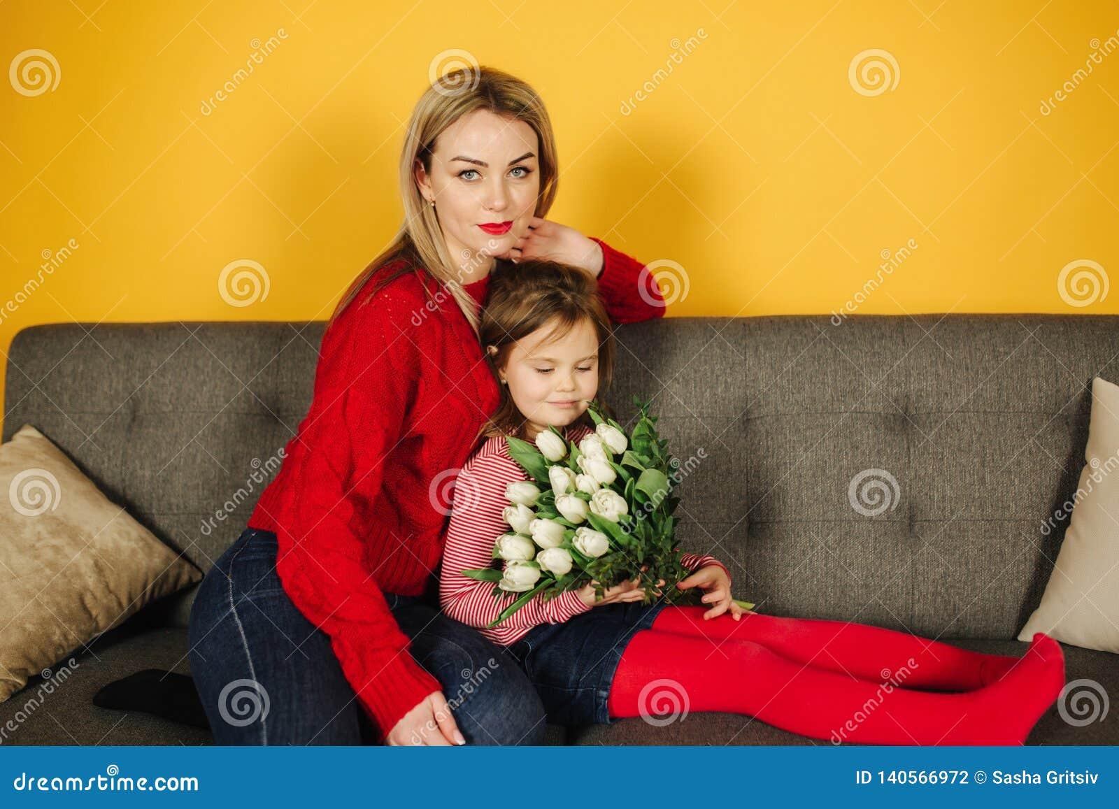 Mãe nova com o doughter que senta-se no sofá cinzento Fundo amarelo no estúdio Flores 8as do março