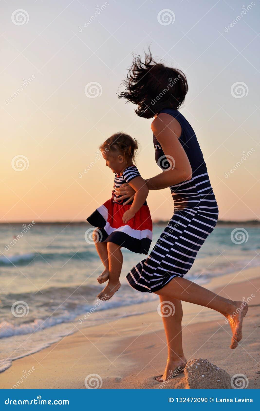 Mãe nova com uma filha pequena que joga na praia