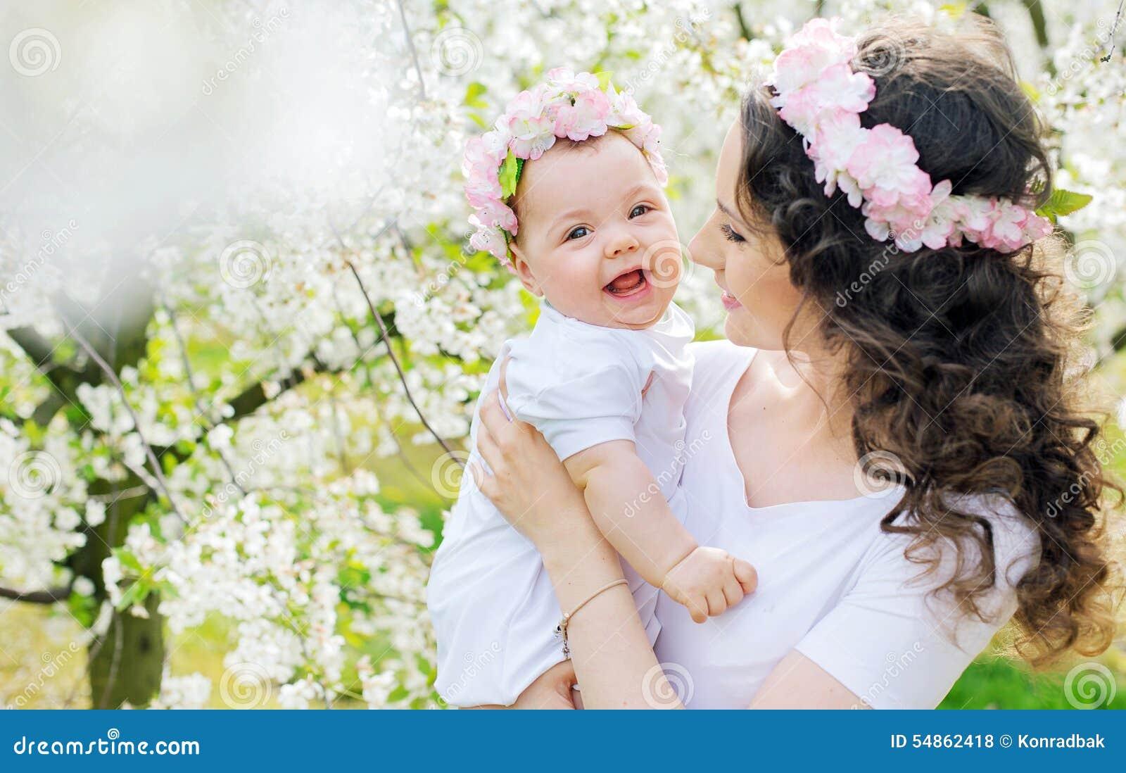 Mãe nova e seu bebê pequeno que relaxam em um pomar da mola