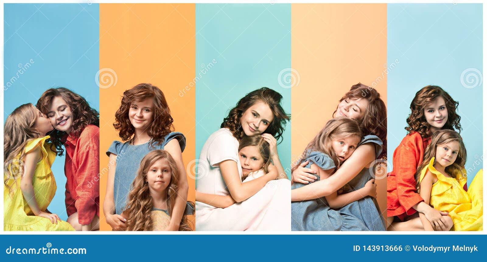 Mãe nova e sua filha pequena que abraçam e que beijam