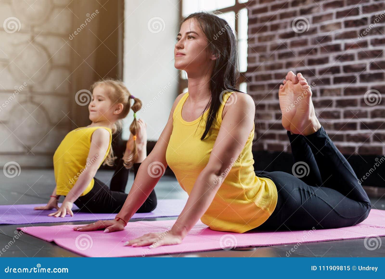 A mãe nova e sua filha que vestem o mesmo sportswear que faz a cobra de rei levantam durante o treinamento da ioga do grupo