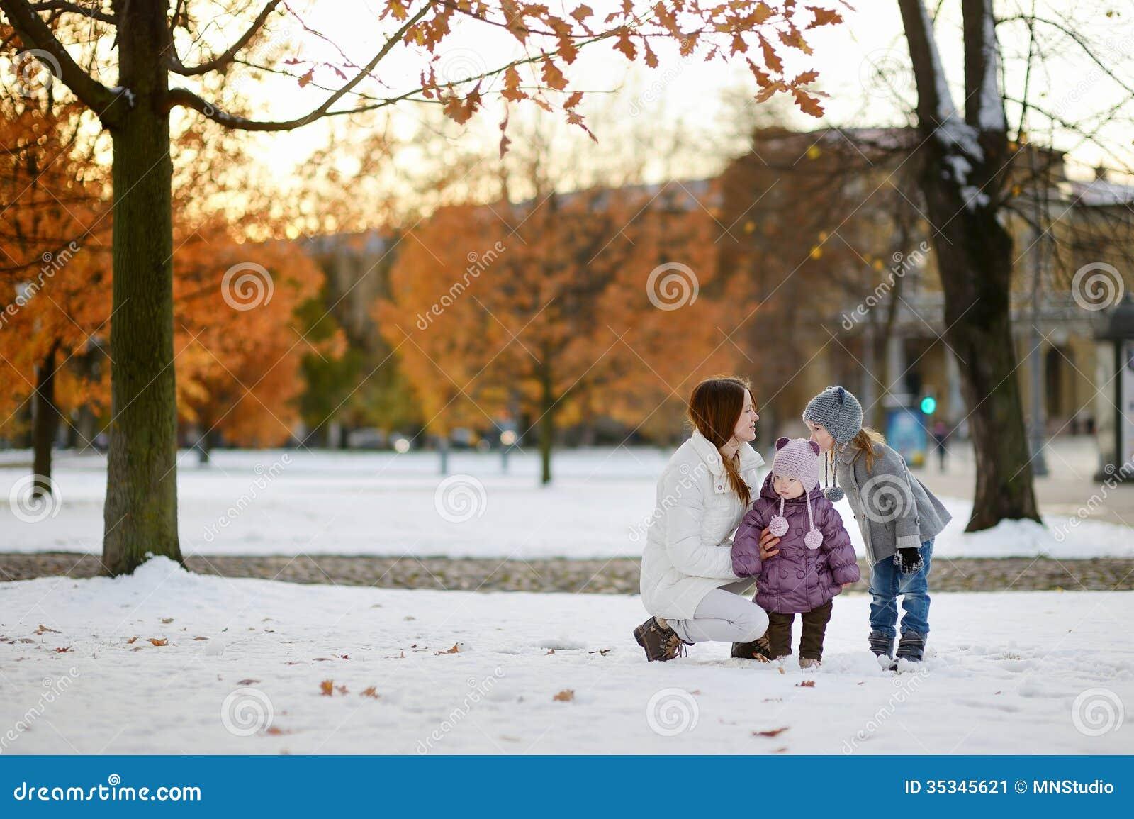 Mãe nova e suas crianças que têm o divertimento no inverno
