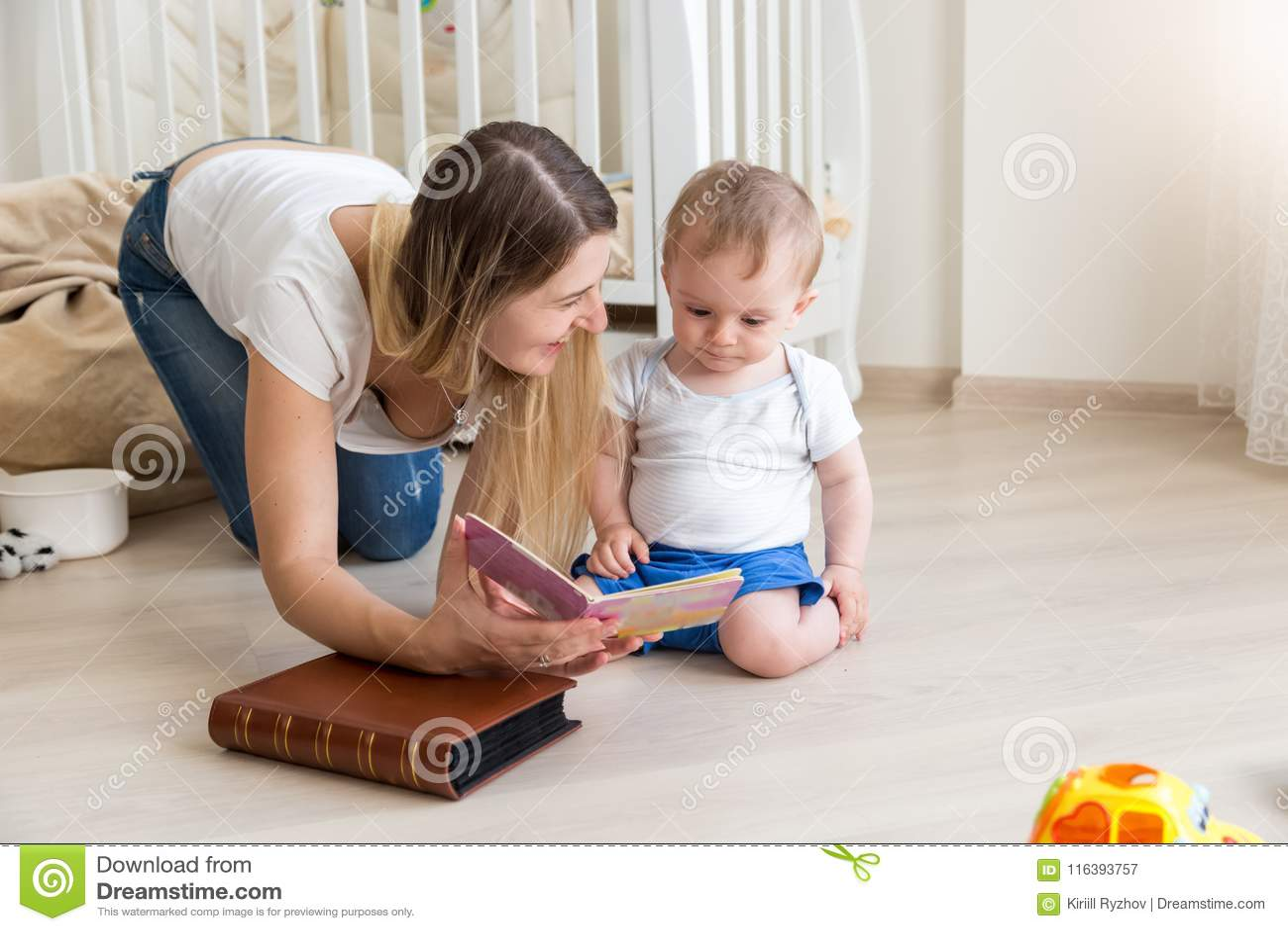 Mãe nova que encontra-se no assoalho com seus menino da criança e livro de leitura
