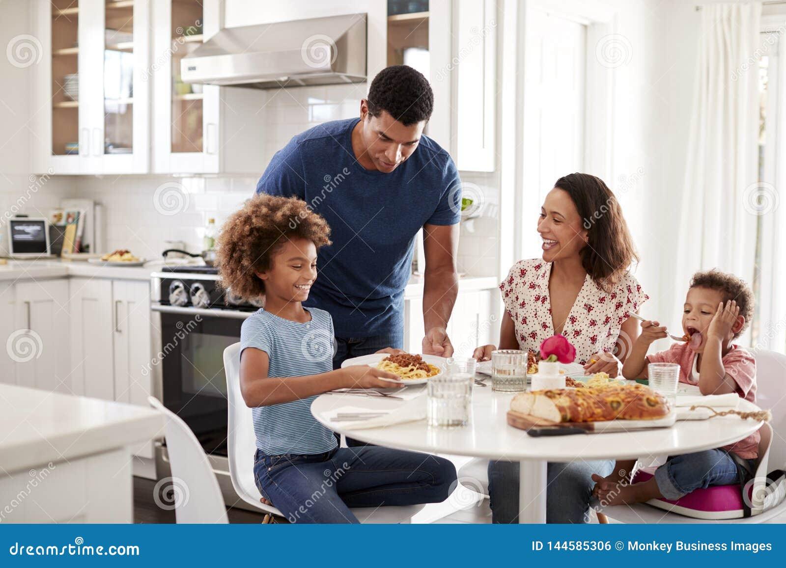 Mãe nova que senta-se na tabela na cozinha com crianças, pai que serve as alimento, foco seletivo