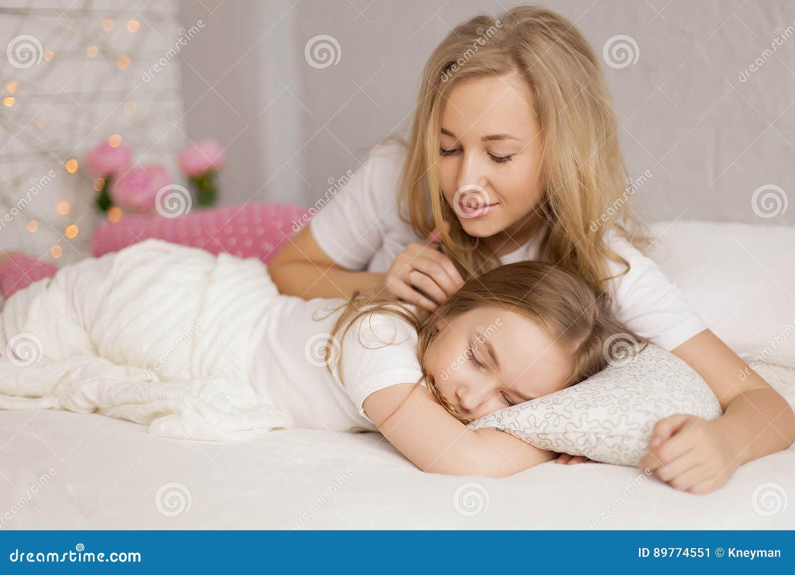 A mãe pôs sua filha para dormir interior Cuidado do conceito