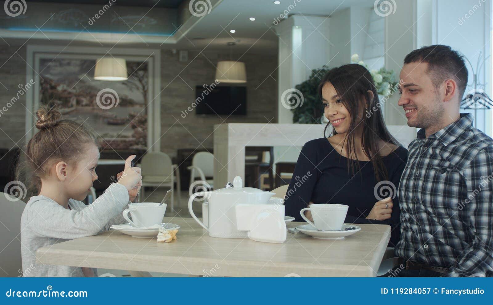 Mãe, pai feliz e menina tendo o jantar no café Caçoe a tomada da foto pelo smartphone quando os pais que levantam sobre