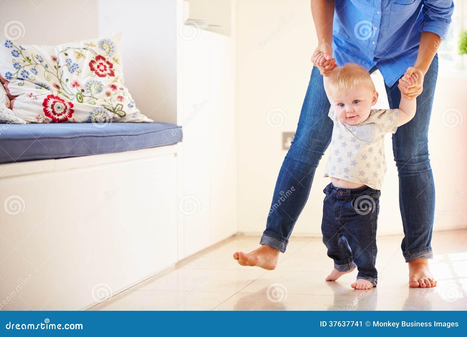 Mãe que ajuda o filho novo como aprende andar