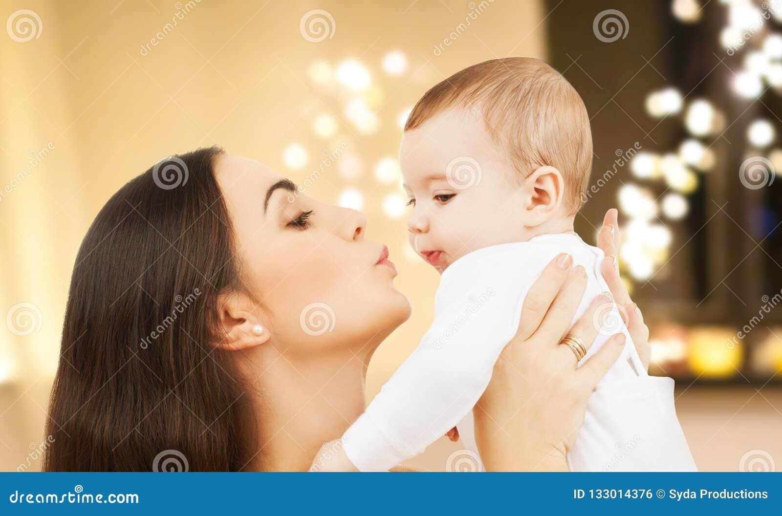 Mãe que beija o bebê sobre luzes de Natal
