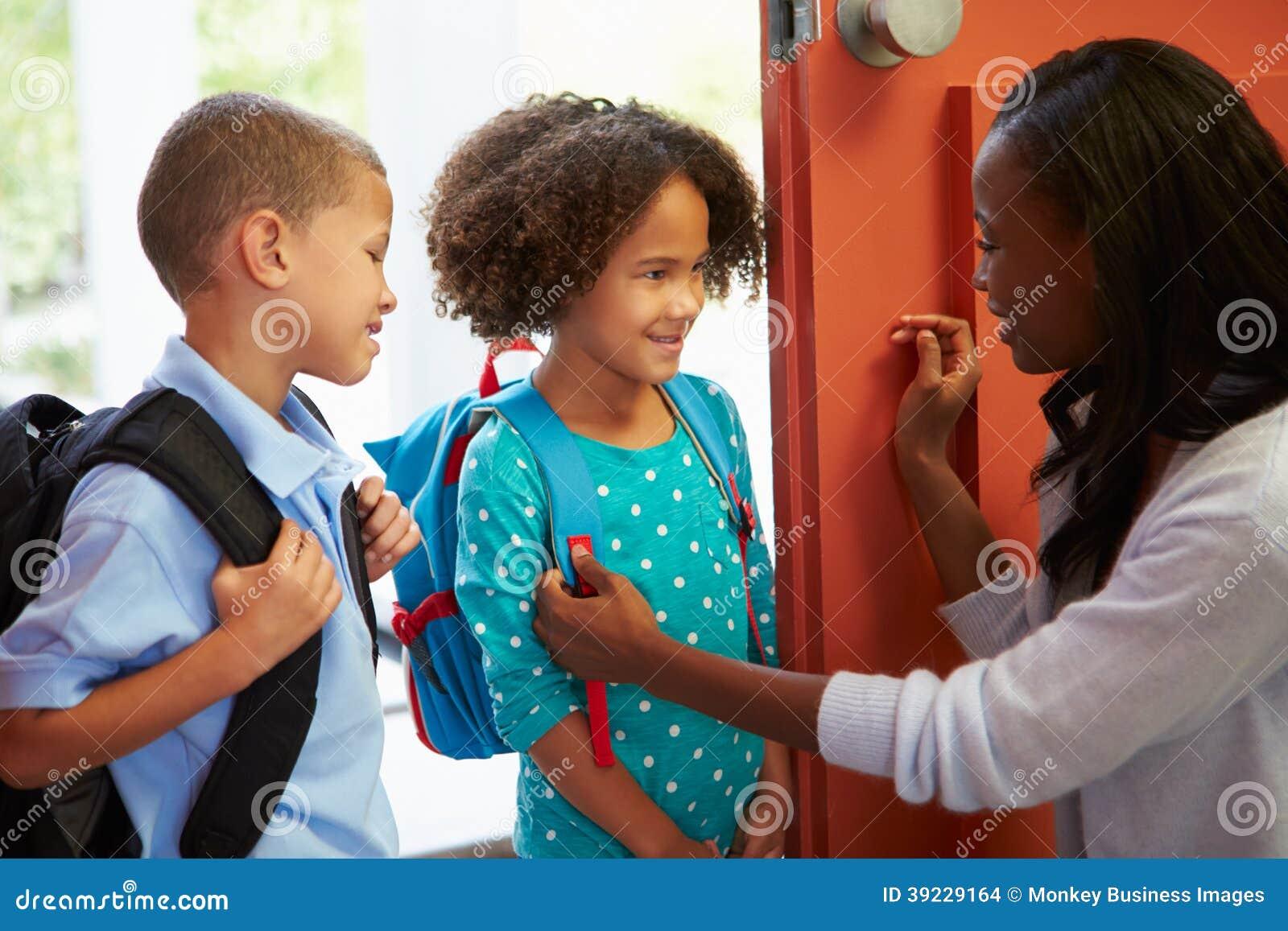 Mãe que diz adeus às crianças como saem para a escola