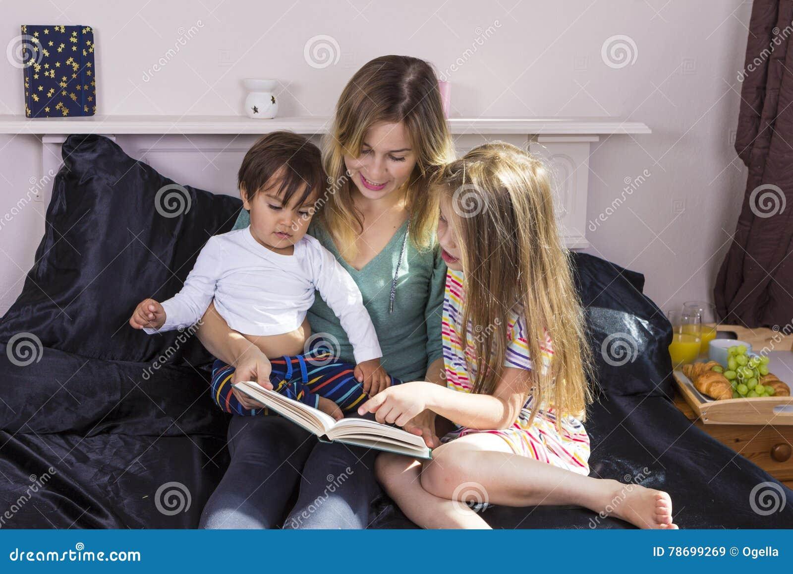 Mãe que lê às crianças na cama