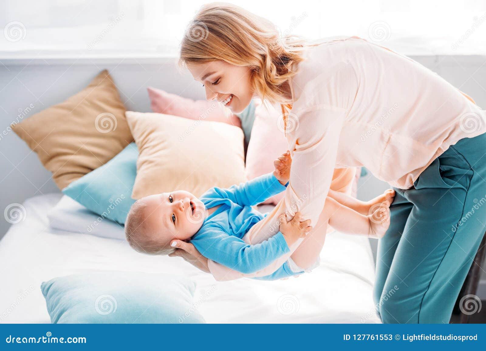 Mãe que leva a criança pequena adorável sobre a cama